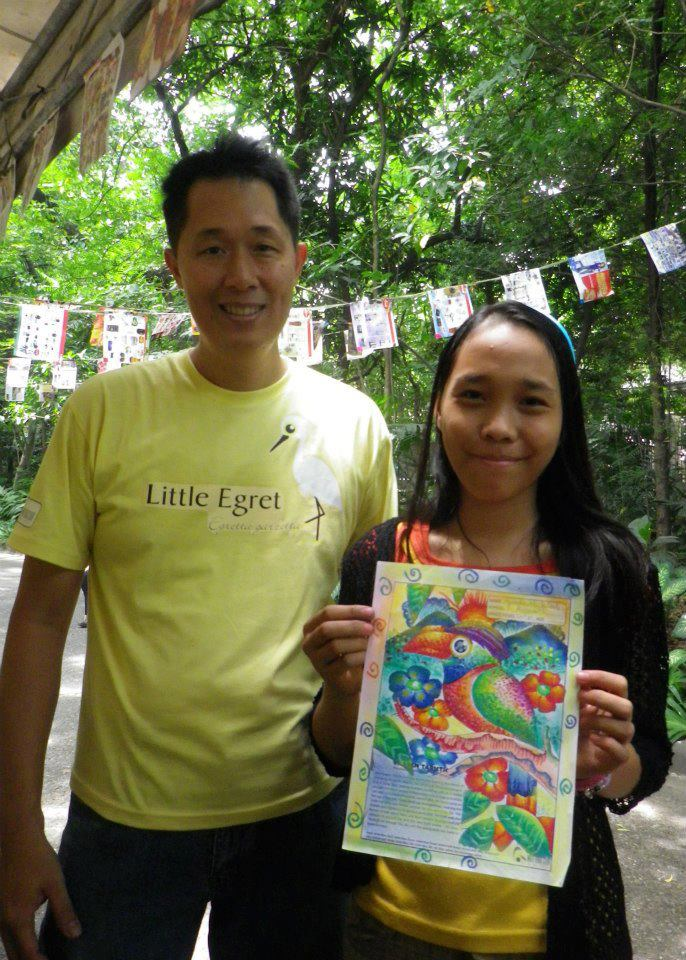 Mike Lu posing with one participant and her finished coloring sheet. Photo by Tinggay Cinco.