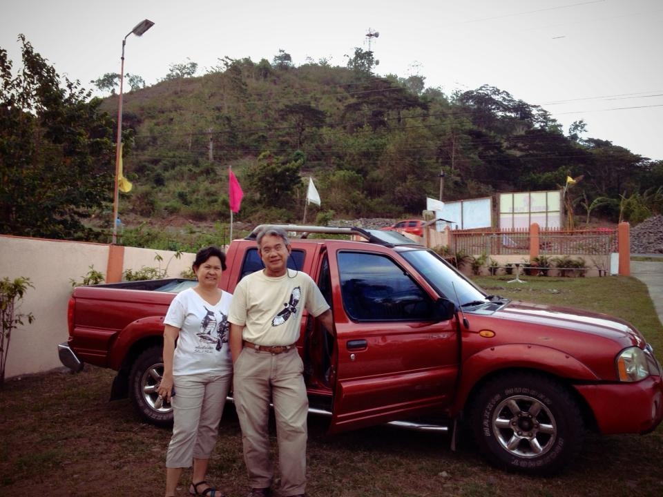 Raptorwatch leads Tere Cervero and Alex Tiongco  in Digos City, Davao del Sur after watching for raptors on the hill in the background. Photo from Tere Cervero.