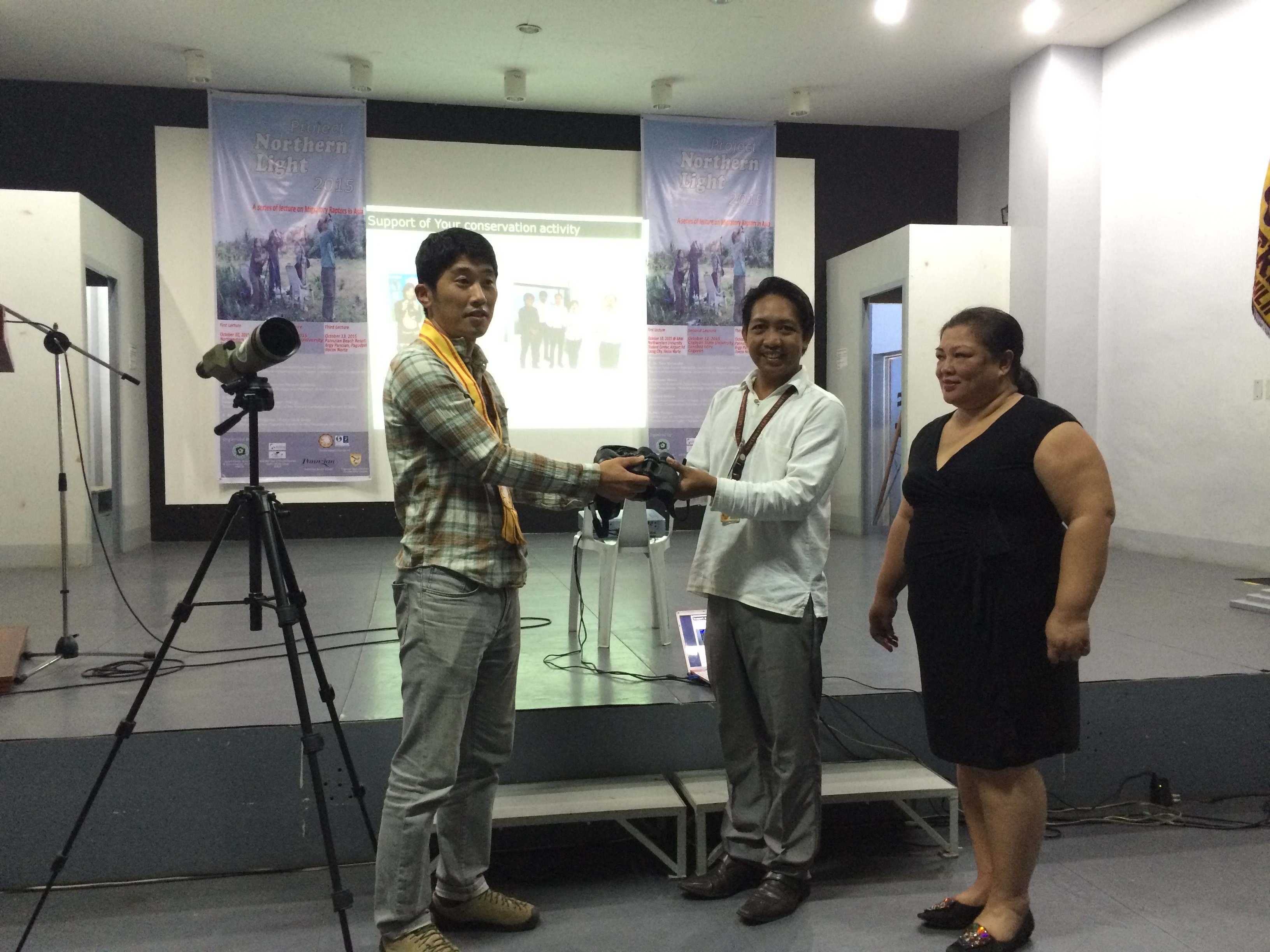 Seiichi Dejima handing over the new binoculars and spotting scope to NWU Michael Calaramo and EVP Ms Lisa Nicolas